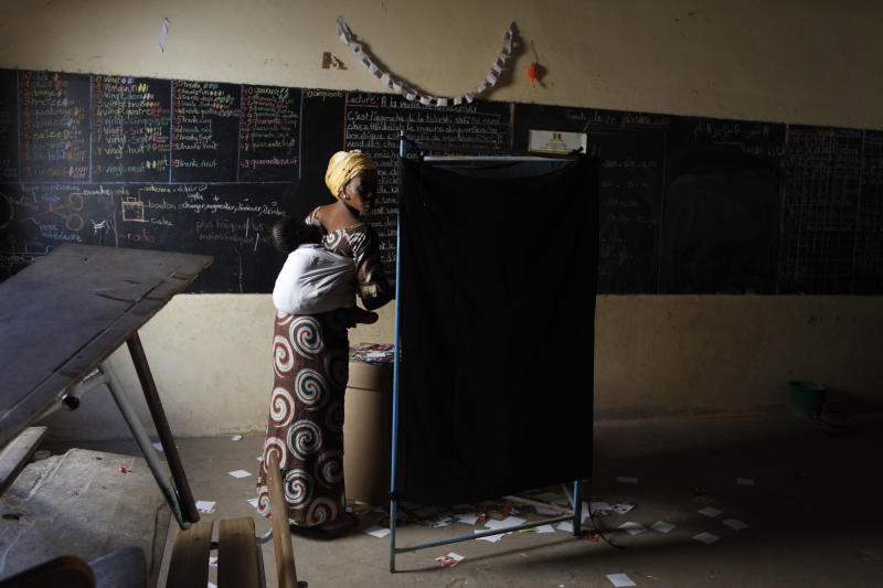 A voter prepares to exit from behind a privacy screen, littered with the ballot papers of candidates not selected by individual voters, at a polling station in the Pikine suburb of Dakar, Senegal Sunday, Feb. 26, 2012. Polling stations have closed and election monitors in Senegal are now counting ballots from a vote that has tested the nation's image as one of the continent's oldest and most robust democracies. Sunday's election follows weeks of protests after the country's highest court ruled 85-year-old President Abdoulaye Wade could run for a third term. (AP Photo/Rebecca Blackwell)