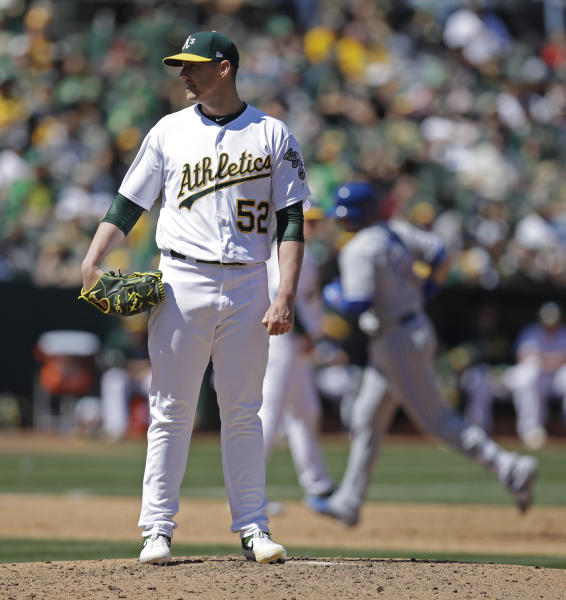 Oakland Athletics' Ryan Buchter (52) waits for Toronto Blue Jays' Justin Smoak to run the bases after giving up a two-run home run to Smoak in the sixth inning of a baseball game Saturday, April 20, 2019, in Oakland, Calif. (AP Photo/Ben Margot)