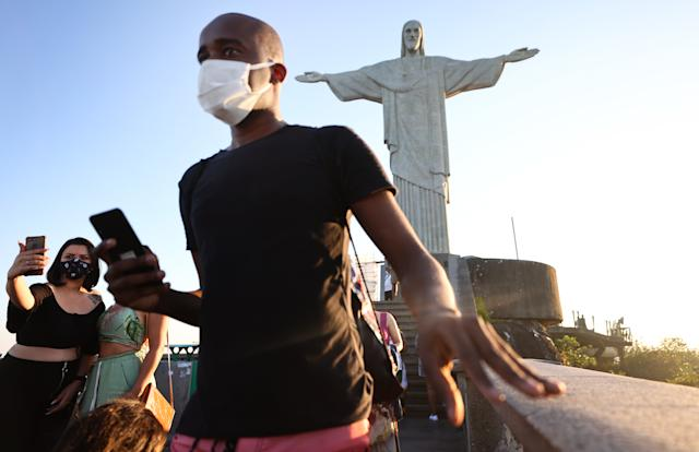 RIO DE JANEIRO, BRAZIL - MAY 27: Christ the Redeemer statue, a top tourist destination, towers over a small number of visitors in face coverings before sunset on May 27, 2021 in Rio de Janeiro, Brazil. Brazil lost $48 billion in revenue from the tourism sector in 2020 due to the COVID-19 pandemic, according to the National Confederation of Trade of Goods, Services and Tourism (CNC). Health experts are warning that Brazil should brace for a new surge of COVID-19 amid a slow vaccine rollout and relaxed restrictions. More than 450,000 people have been killed in Brazil by COVID-19, second only to the U.S. (Photo by Mario Tama/Getty Images)