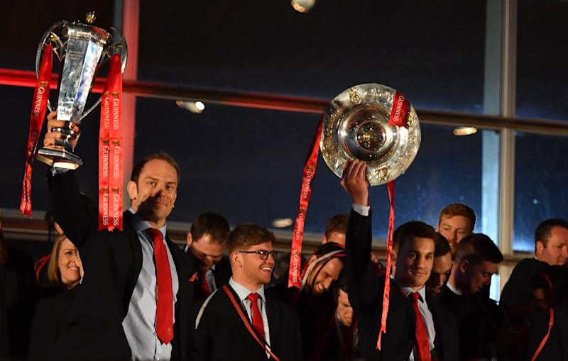 Wales captain Alun Wyn Jones (left) and Jonathan Davies lift the Six Nations trophy and Triple Crown trophy during the 2019 Guinness Six Nations Grand Slam winners celebration welcome at the Senedd in Cardiff Bay. (Photo by Simon Galloway/PA Images via Getty Images)