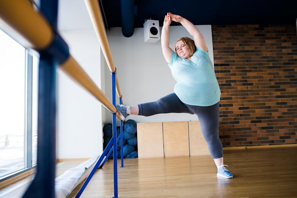 Full length portrait of graceful obese woman stretching legs in ballet class by window, copy space