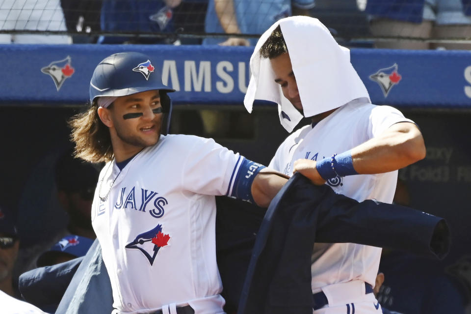 Toronto Blue Jays' Lourdes Gurriel Jr., right, puts The Blue Jacket on Bo Bichette after Bichette's two-run home run in the first inning of a baseball game against the Minnesota Twins in Toronto on Sunday, Sept. 19, 2021. (Jon Blacker/The Canadian Press via AP)