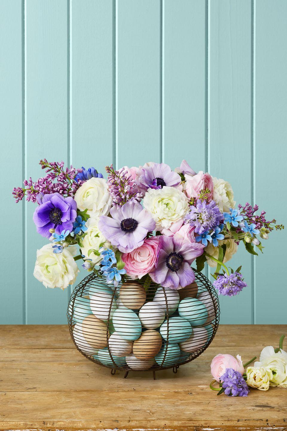 """<p>A vintage French egg collecting basket filled with colorful wooden eggs makes the perfect home for displaying your abundant spring bouquet (here are lilacs, anemones, Scabiosa lavender, allium, and ranunculus).</p><p><strong>To make:</strong> Dye or paint wooden eggs white or robin's egg blue. You can also leave a few natural. Place a vase inside the basket and surround with eggs. Fill vase with water and flowers. </p><p><a class=""""link rapid-noclick-resp"""" href=""""https://www.amazon.com/Unfinished-Unpainted-Wooden-Easter-Decorate/dp/B083GG6VQ9/ref=sr_1_7?tag=syn-yahoo-20&ascsubtag=%5Bartid%7C10050.g.1111%5Bsrc%7Cyahoo-us"""" rel=""""nofollow noopener"""" target=""""_blank"""" data-ylk=""""slk:SHOP WOODEN EGGS"""">SHOP WOODEN EGGS</a></p>"""