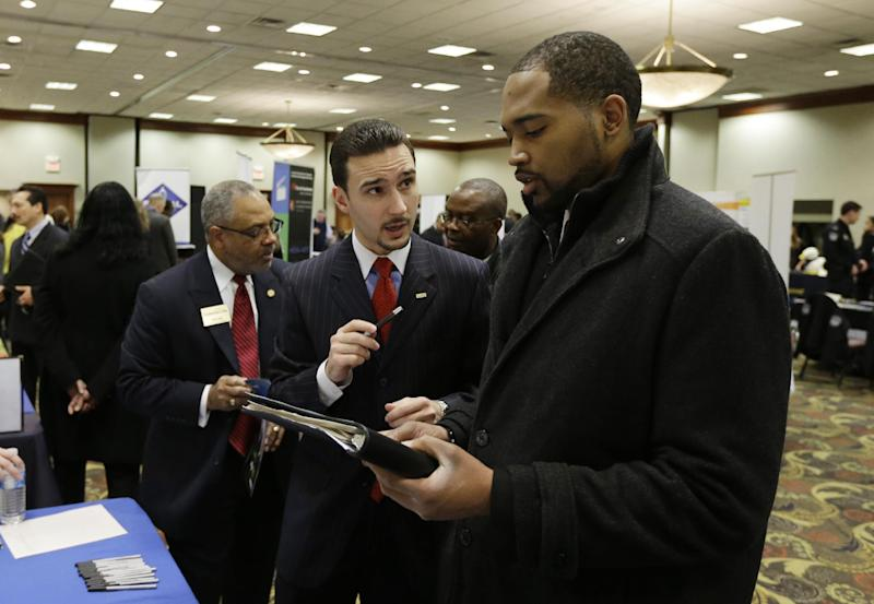 In this Feb. 28, 2013 photo Robin Basil, left, of the Garland-Hill insurance agency talks with college student Markell Easter at the JobFairGiant.com employment fair in Dearborn, Mich. Fewer Americans sought unemployment aid last week, reducing the average number of weekly applications last month to a five-year low. The drop shows that fewer layoffs are strengthening the job market. The Labor Department said Thursday, March 14, 2013 that applications fell 10,000 to a seasonally adjusted 332,000. That cut the four-week average to 346,750, the lowest since March 2008, just several months after the Great Recession began. (AP Photo/Carlos Osorio)