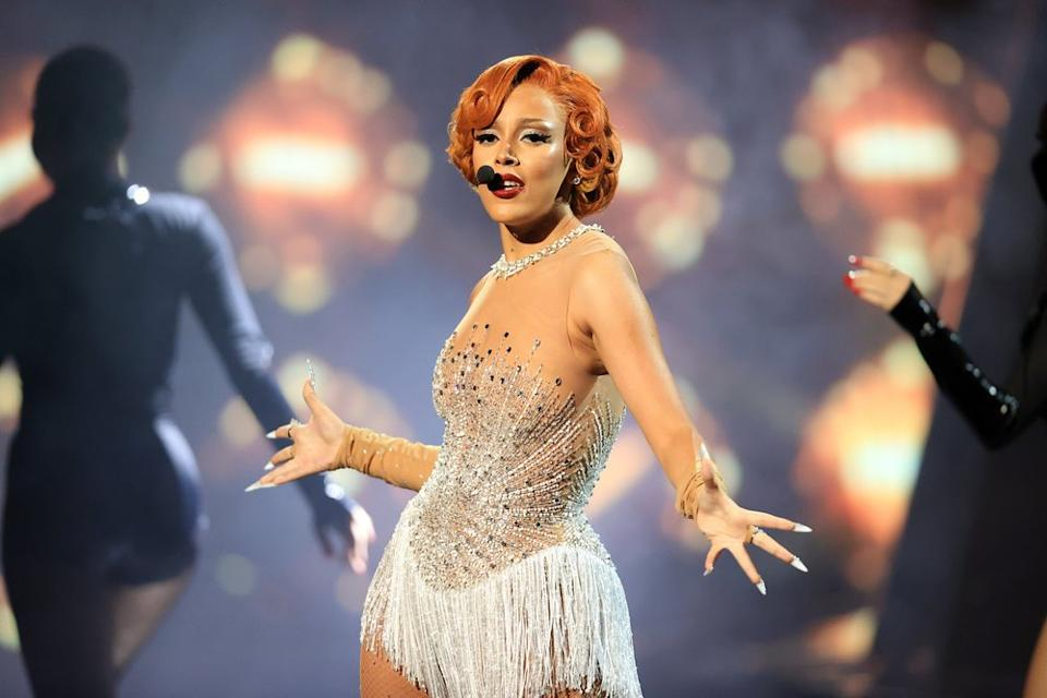 Doja Cat in a sequined, fringed costume, performs.