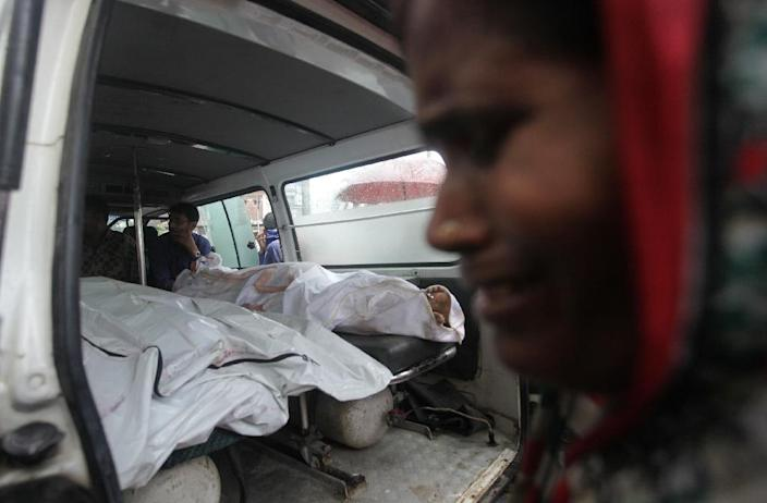 A mourner cries next to the bodies of factory workers after an explosion in a factory in Tongi, Bangladesh, on September 10, 2016 (AFP Photo/Rajib Dhar)