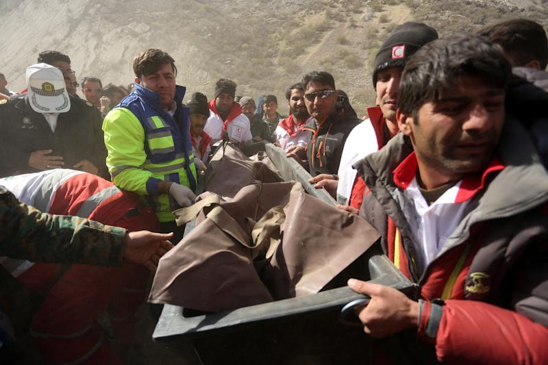 Medics and rescuers evacuate the body of a victim killed in a private plane crash in Iran, March 12, 2018. The crash killed 11 people, including a Turkish tycoon's daughter. (Tasnim News Agency / Reuters)