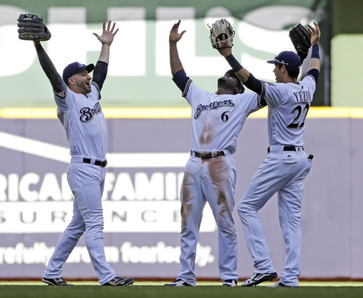 Milwaukee Brewers, from left, Ryan Braun, Lorenzo Cain and Christian Yelich celebrate after a baseball game against the Chicago Cubs, Wednesday, June 13, 2018, in Milwaukee. The Brewers won 1-0. (AP Photo/Aaron Gash)