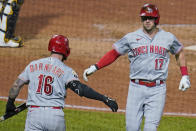 Cincinnati Reds' Kyle Farmer (17) is congratulated by Tucker Barnhart as Farmer returns to the dugout after hitting a solo home run off Pittsburgh Pirates relief pitcher Sam Howard during the eighth inning of a baseball game in Pittsburgh, Wednesday, Sept. 15, 2021. (AP Photo/Gene J. Puskar)