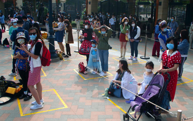Visitors, wearing face masks, wait to enter the Disneyland theme park in Shanghai as it reopened, Monday, May 11, 2020. Visits will be limited initially and must be booked in advance, and the company said it will increase cleaning and require social distancing in lines for the various attractions. With warmer weather and new coronavirus cases and deaths falling to near-zero, China has been reopening tourist sites such as the Great Wall and the Forbidden City palace complex in Beijing. (AP Photo/Sam McNeil)