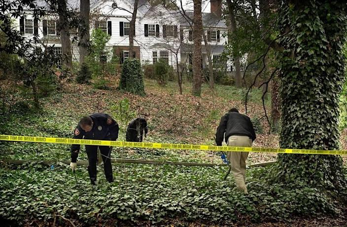 Durham Police Department officers search for evidence in the front yard of Michael Peterson's home. Peterson's wife, Kathleen Hill Peterson, was found dead at the bottom of a staircase in the home on December 10, 2001. Peterson called 911 and said that he believed his wife fell down the stairs after coming inside from the couple's backyard.