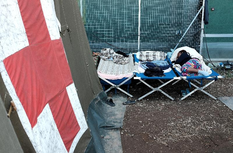 Migrants sleep outside a tent at a refugee camp next to the Tiburtina train station in Rome on August 20, 2015 (AFP Photo/Alberto Pizzoli)