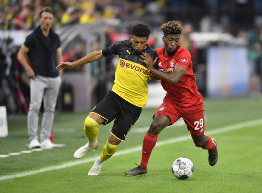 FILE - In this Saturday, Aug. 3, 2019 file photo Bayern's Kingsley Coman, right, duels for the ball with Dortmund's Jadon Sancho, left, during the German Supercup final soccer match between Borussia Dortmund and Bayern Munich in Dortmund, Germany. Borussia Dortmund has declared a challenge to end Bayern Munichs seven-year domination of the Bundesliga, encouraged by signs of disharmony and unrest from the defending champions. In the background is Bayern's head coach Niko Kovac. (AP Photo/Martin Meissner)