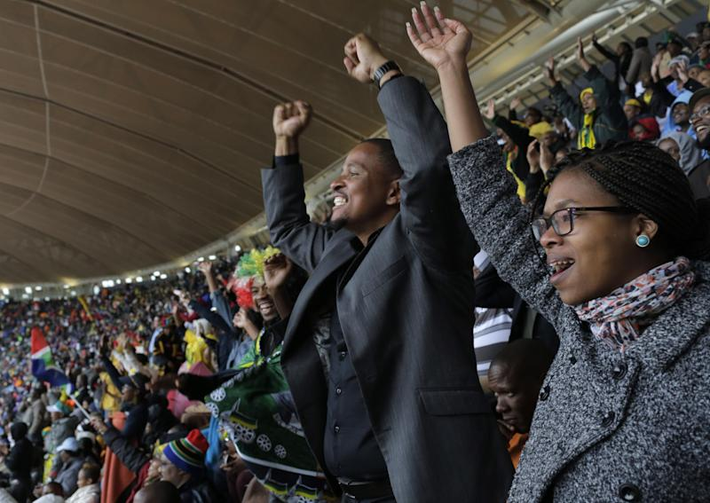 People stand up and cheer during the memorial service for former South African president Nelson Mandela at the FNB Stadium in Soweto, near Johannesburg, South Africa, Tuesday Dec. 10, 2013. (AP Photo/Bernat Armangue)
