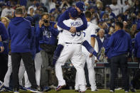 The Los Angeles Dodgers celebrate after Chris Taylor hit a home run during the ninth inning to win a National League Wild Card playoff baseball game 3-1 over the St. Louis Cardinals Wednesday, Oct. 6, 2021, in Los Angeles. Cody Bellinger also scored. (AP Photo/Marcio Jose Sanchez)