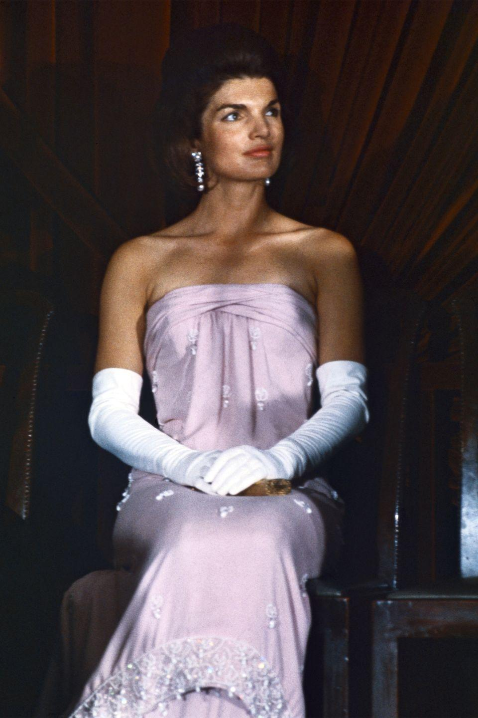 <p>Jackie looked regal in a strapless lavender gown, diamond drop earrings, and long white gloves during a ceremony at the National Gallery of Art. </p>