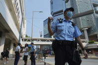 """Police officers walk outside a court as they wait for Tong Ying-kit's arrival at a court in Hong Kong Tuesday, July 27, 2021. Hong Kong High Court will deliver verdict in the afternoon for the first person charged under Hong Kong's National Security Law. Tong was arrested in July 2020 after driving his motorbike into a group of police officers while carrying a flag bearing the protest slogan """"Liberate Hong Kong."""" He was charged with inciting separatism and terrorism. (AP Photo/Vincent Yu)"""