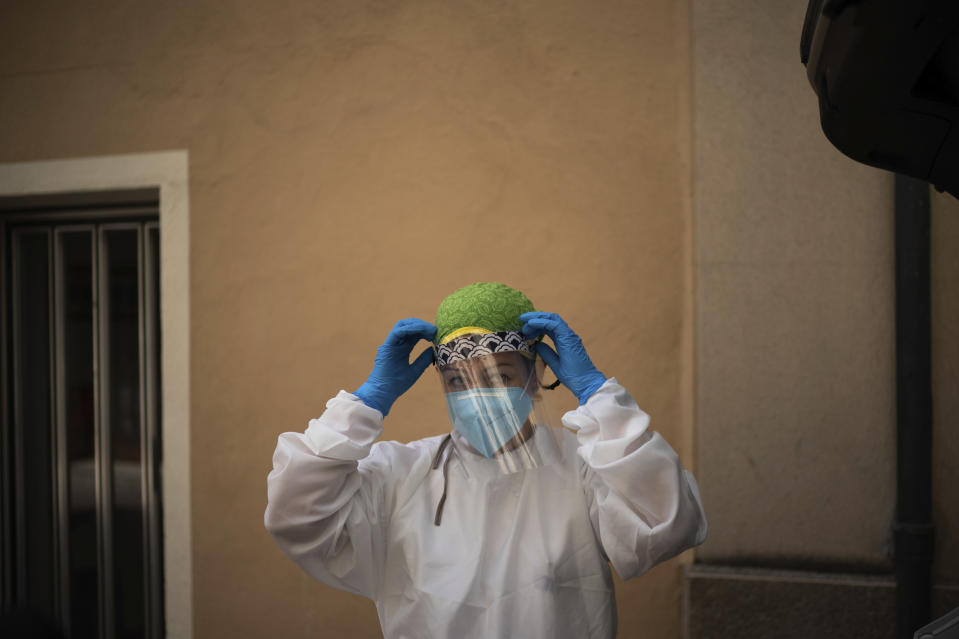In this July 31, 2020 file photo, Dr. Marta Ruberte prepares to visit an elderly patient at home in Sant Sadurní d'Anoia, Catalonia region, Spain. In contrast to the darkest weeks of March and April, when the virus ripped through Spain's elderly in nursing homes and pushed the country's hospitals to the breaking point, the pressure is now on Spain's neighborhood health clinics. (AP Photo/Felipe Dana)
