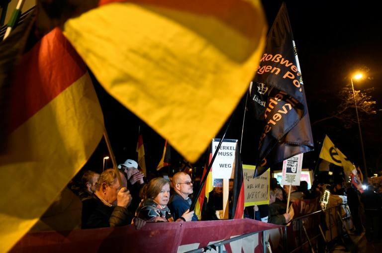 """Far-right protesters also marched during the Merkel visit, with placards bearing slogans such as """"Merkel has to go"""""""
