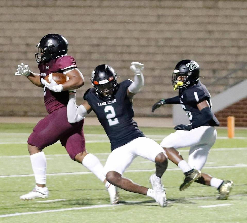 Timberview running back Deuce Jones (2) rumbles to the end zone for the winning score defended by Lake Ridge cornerbacks Marvin Covington (2) and Darrell James (26) during Thursday's game at Vernon Newsom Stadium in Mansfield. Timberview defeated Lake Ridge 28-14.