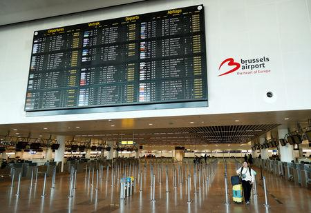 A stranded passenger walks under a flight information board displaying cancelled flights during a strike by Belgian trade unions at Zaventem international airport near Brussels, Belgium, February 13, 2019.  REUTERS/Francois Lenoir