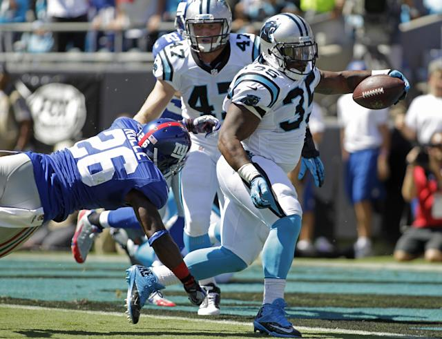 Carolina Panthers fullback Mike Tolbert (35) runs past New York Giants strong safety Antrel Rolle (26) for a touchdown during the first half of an NFL football game in Charlotte, N.C., Sunday, Sept. 22, 2013. (AP Photo/Bob Leverone)