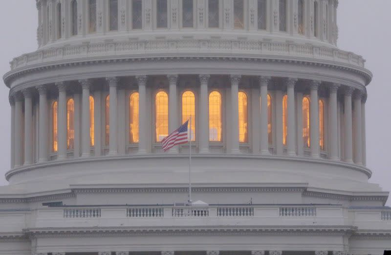 FILE PHOTO: A United States flag flies in front of the U.S. Capitol dome at sunrise in Washington