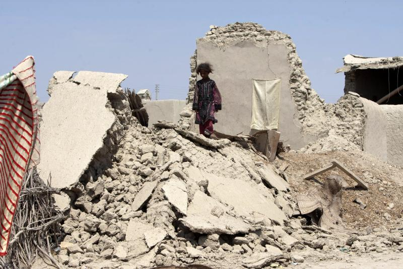 A Pakistani girl walks on the rubble of a house destroyed following an earthquake in Labach, the remote district of Awaran in Baluchistan province, Pakistan, Thursday, Sept. 26, 2013. Two days after the tremor struck, rescuers were still struggling to help survivors. The death toll from the quake reached in hundreds on Thursday, with more than 500 people injured. (AP Photo/Shakil Adil)