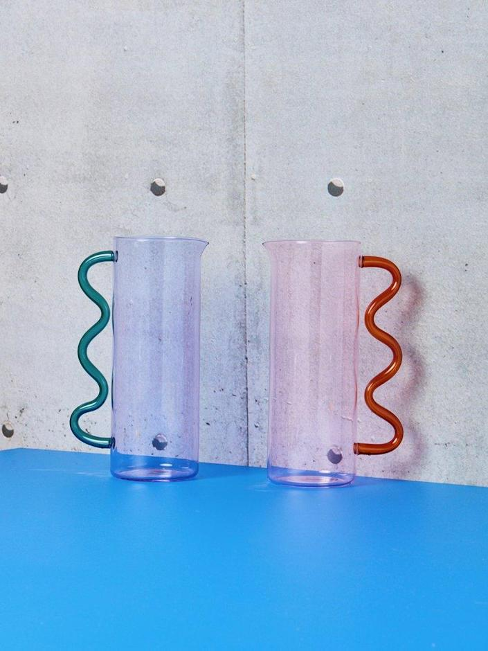 """Sophie Lou Jacobsen, the woman behind our favorite <a href=""""https://www.architecturaldigest.com/gallery/best-glassware-sets?mbid=synd_yahoo_rss"""" rel=""""nofollow noopener"""" target=""""_blank"""" data-ylk=""""slk:ripple glasses"""" class=""""link rapid-noclick-resp"""">ripple glasses</a>, applies her colorful, creative mind to this borosilicate glass pitcher, available at Coming Soon in New York. $215, Coming Soon. <a href=""""https://comingsoonnewyork.com/products/wave-pitcher?variant=31908102799462"""" rel=""""nofollow noopener"""" target=""""_blank"""" data-ylk=""""slk:Get it now!"""" class=""""link rapid-noclick-resp"""">Get it now!</a>"""
