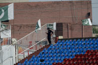 A Pakistani police officer stands guard an enclosure in the Pindi Cricket Stadium before the start of the first one day international cricket match between Pakistan and New Zealand, in Rawalpindi, Pakistan, Friday, Sept. 17, 2021. The limited-overs series between Pakistan and New Zealand has been postponed due to security concerns of the Kiwis. (AP Photo/Anjum Naveed)