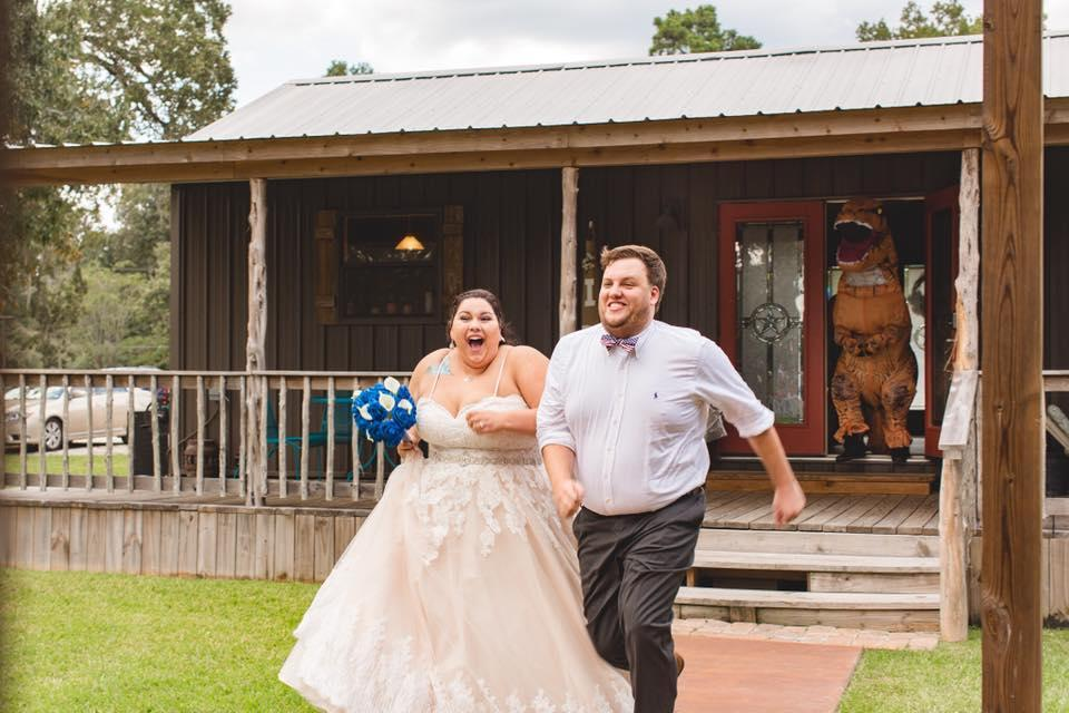 Newlyweds Erin Williams and Rob Cole get chased into their reception by a T. rex. (Photo: D2 Pictures)
