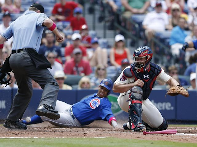 Chicago Cubs' Starlin Castro, center, scores on a Nate Schierholtz base hit as the ball gets past Atlanta Braves catcher Evan Gattis, right, in the fourth inning of a baseball game on Sunday, May 11, 2014, in Atlanta. (AP Photo/John Bazemore)