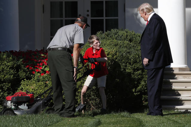 <p>Frank Giaccio, 11, of Falls Church, Va., turns his head as he is surprised by President Donald Trump while mowing the lawn of the Rose Garden, Friday, Sept. 15, 2017, at the White House in Washington. The 11-year-old, who wrote the president requesting to mow the lawn at the White House, was so focused on the job at hand the he didn't notice the president until he was right next to him. At left is a member of the National Park Service. (Photo: Jacquelyn Martin/AP) </p>