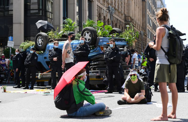 """Protesters of the environmental protest movement """"Extinction Rebellion"""" sit next to a car placed upside down on a trailer, in Berlin"""