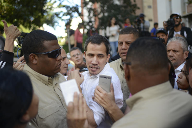 Bodyguards escort opposition leader Juan Guaido away from an outdoor event where he spoke to supporters in the Montalban neighborhood of Caracas, Venezuela, Saturday, Jan. 11, 2020. Venezuelans are deciding whether or not to heed Guaido's call for a new round of protests amid skepticism that he can still mobilize large numbers, and an estimated 4.5 million people have fled the country. (AP Photo/Matias Delacroix)