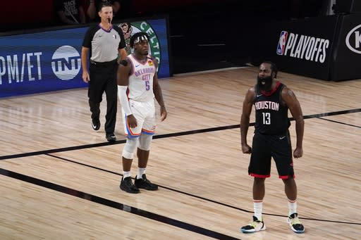 Referee Pat Fraher, left, and Oklahoma City Thunder's Luguentz Dort (5) look on as Houston Rockets' James Harden (13) celebrates after blocking a 3-point shot attempt by Dort during the second half of an NBA first-round playoff basketball game in Lake Buena Vista, Fla., Wednesday, Sept. 2, 2020. (AP Photo/Mark J. Terrill)