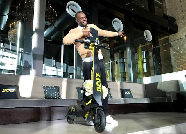Olympic gold medallist Usain Bolt poses for a photograph as he shows off an electric scooter at a launch event in Tokyo
