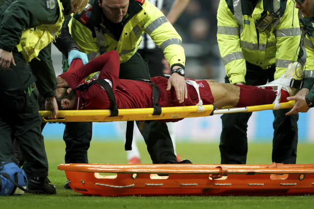 Liverpool's Mohamed Salah receives treatment after an injury during a Premier League match against Newcastle United at St James' Park, Newcastle, England, Saturday May 4, 2019. (Owen Humphreys/PA via AP)