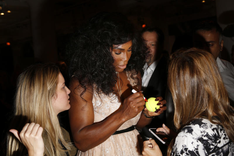 Serena Williams, center, signs a tennis ball for a fan before showing her Serena Williams Signature Statement Spring 2017 collection during Fashion Week in New York, Monday, Sept. 12, 2016. (AP Photo/Seth Wenig)