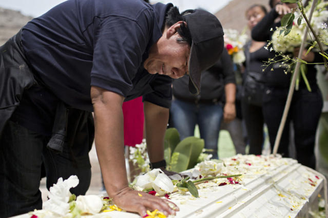 <p>Evila cries and talks to Tamara before her coffin is placed in the grave. (Photo: Danielle Villasana) </p>