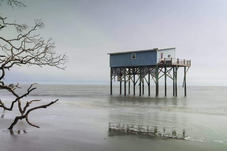 A cabin raised several feet above the sea water on stilts.