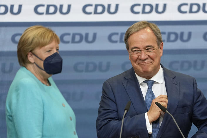 Chancellor Angela Merkel stands next to Governor Armin Laschet, right, the top CDU candidate after the German parliament elections at the Christian Democratic Union, CDU, party's headquarters in Berlin, Sunday, Sept. 26, 2021. German voters are choosing a new parliament in an election that will determine who succeeds Chancellor Angela Merkel after her 16 years at the helm of Europe's biggest economy. (AP Photo/Martin Meissner)