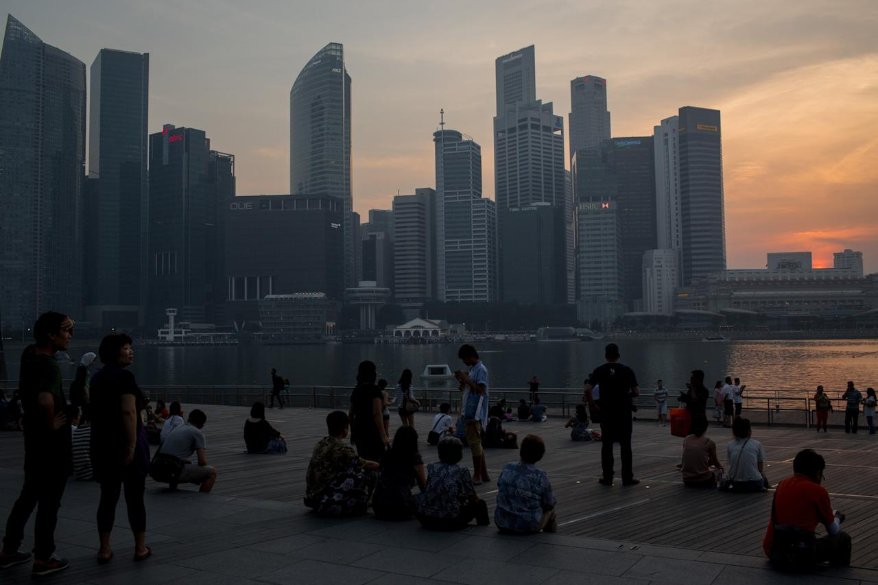 "SINGAPORE - JUNE 22: People sit and watch the sun set over the Singapore skyline on June 22, 2013 in Singapore. As skies cleared the Pollutant Standards Index (PSI) dropped to 73 Saturday afternoon, the lowest rating in six days. Earlier in the week the PSI reached the highest level on record at 401 covering Singapore in a thick ""hazardous"" haze caused by deliberate slash-and-burn forest fires started by companies in neighbouring Sumatra. (Photo by Chris McGrath/Getty Images)"