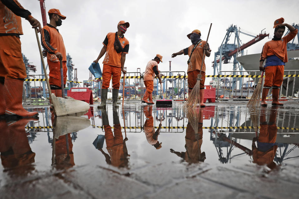 Workers dry a dock at the Tanjung Priok Port where the command center for the search and rescue mission for Sriwijaya Air flight SJ-182 that crashed into the Java Sea on Jan. 9 is located, at Tanjung Priok Port in Jakarta, Indonesia, Thursday, Jan. 21, 2021. Indonesian authorities on Thursday ended the search for the wreckage of the plane that nose-dived into the sea, killing all of its passengers on board. (AP Photo/Dita Alangkara)