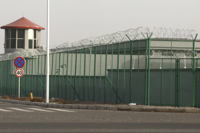 """FILE - In this Monday, Dec. 3, 2018, file photo, a guard tower and barbed wire fences surround an internment facility in the Kunshan Industrial Park in Artux in western China's Xinjiang Uyghur Autonomous Region. A spokesperson for the Xinjiang region called accusations of genocide """"totally groundless"""" as the British parliament approved a motion Thursday, April 22, 2021 that said China's policies amounted to genocide and crimes against humanity. (AP Photo/Ng Han Guan, File)"""