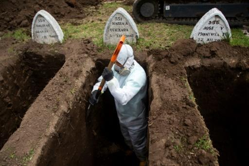A worker wearing biosecurity equipment digs graves for alleged victims of the new coronavirus Covid-19, at the San Diego Cemetery in Quito