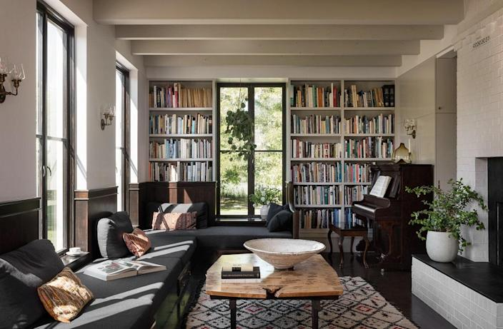 The living room is filled with books and plants. Many pieces of furniture and decorative accessories are either custom creations or vintage finds. The wall paint throughout is Benjamin Moore White Opulence.