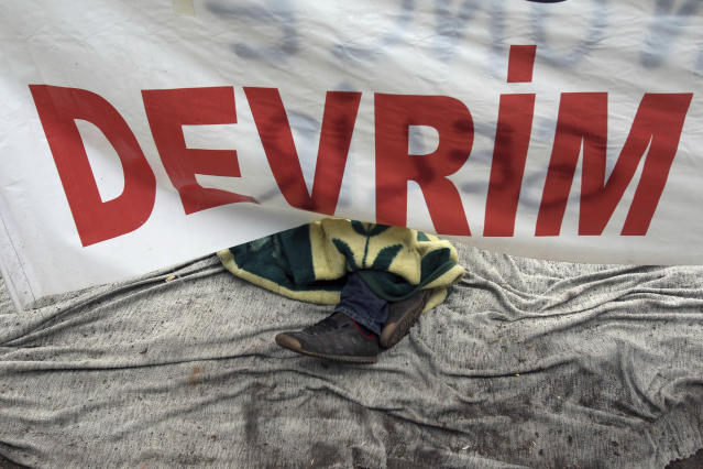A protester sleeps under a banner that reads ''Revolution'' at the Gezi Park in Istanbul, Turkey, early Wednesday, June 12, 2013. Riot police fired tear gas, water cannon and rubber bullets in day-long clashes that lasted into the early hours Wednesday, battling protesters who have been occupying Istanbul's central Taksim Square and its adjacent Gezi Park in the country's most severe anti-government protests in decades. (AP Photo/Thanassis Stavrakis)