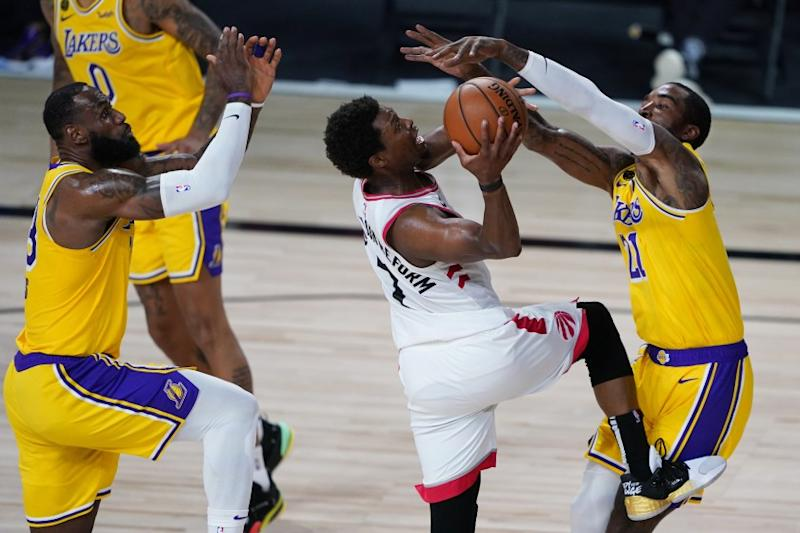 Los Angeles Lakers' LeBron James, left, and JR Smith, right, guard Toronto Raptors' Kyle Lowry during the second half of an NBA basketball game Saturday, Aug. 1, 2020, in Lake Buena Vista, Fla. (AP Photo/Ashley Landis, Pool)