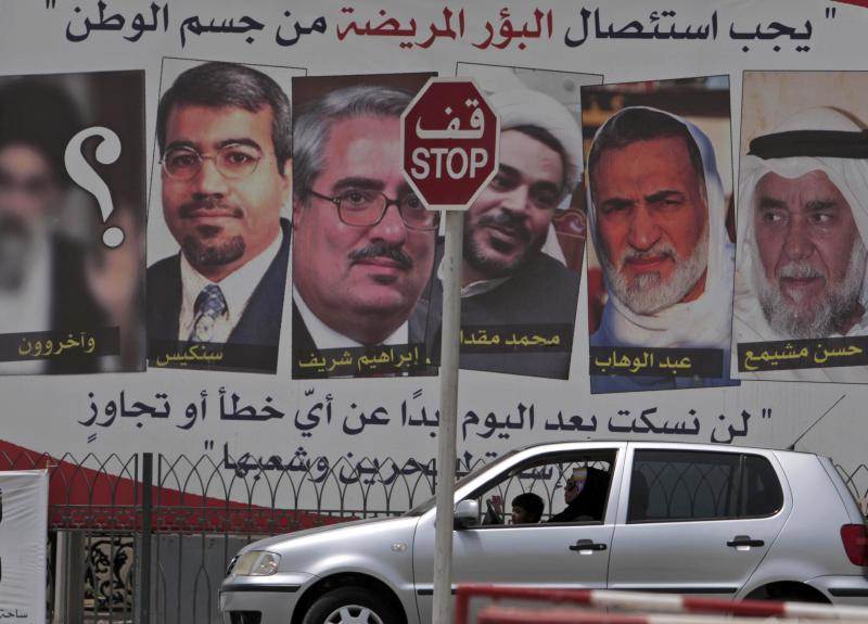 "A car passes a pro-government billboard Sunday, May 8, 2011, in Muharraq, Bahrain, with pictures of jailed Bahraini Shiite and Sunni opposition leaders with their names written below, right to left: Hassan Meshaima, Abdel Wahab Hussein, Mohamed Muqdad, Ibrahim Sharif, Abdel Jalil Singace and a question mark over a blurred picture depicting a Shiite cleric that reads beneath it ""And others."" At top, the sign reads: ""Disease must be excised from the body of the nation,"" and at bottom: ""We won't keep quiet after today about any mistakes or excesses by those whom abuse Bahrain and its people."" Bahrain's military prosecutor accused 21 political activists Sunday, including those on the billboard, of seeking to overthrow the ruling monarchy with the help of a foreign terrorist group, an apparent reference to Iranian-backed militants in a widening crackdown on a pro-reform uprising led by the island nation's Shiite majority. (AP Photo/Hasan Jamali)"